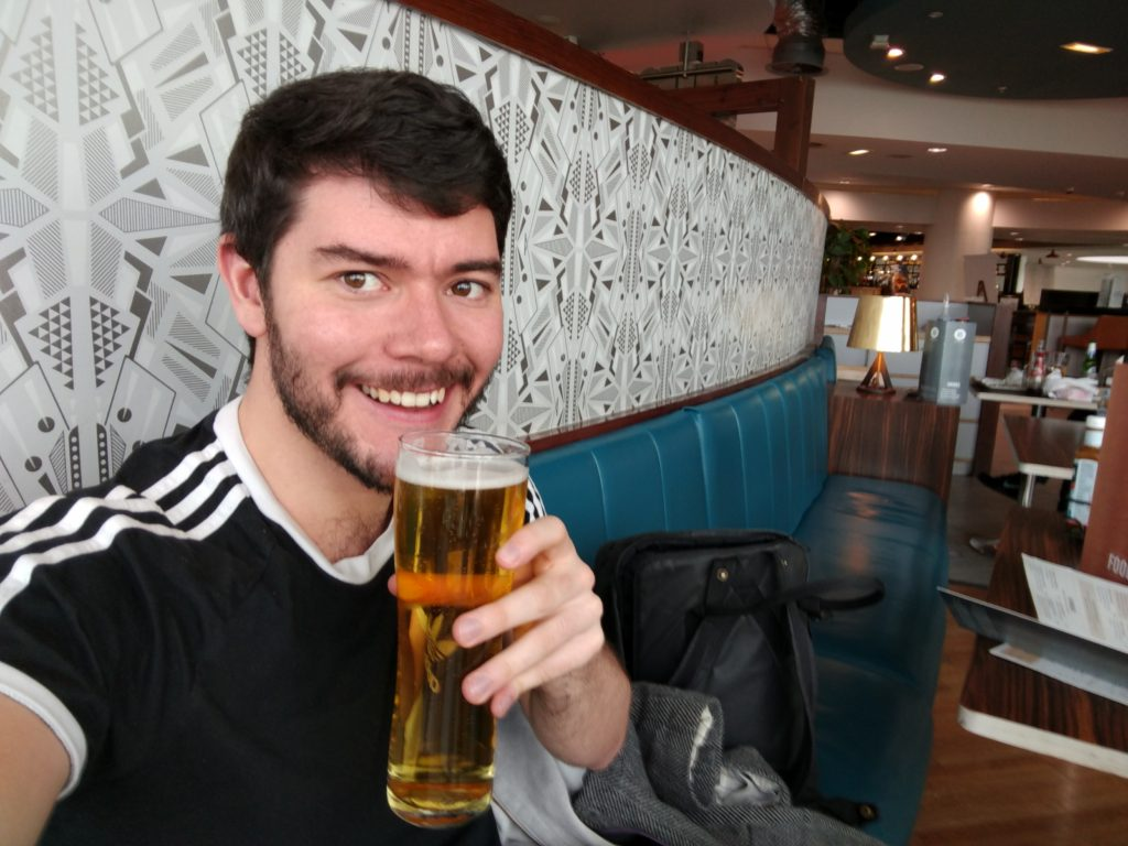 Jack holding a beer in Manchester Airport.
